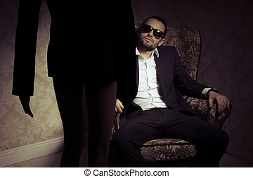 Young and elegant man sitting in chair looking at woman standing in front of him isolated over vintage background