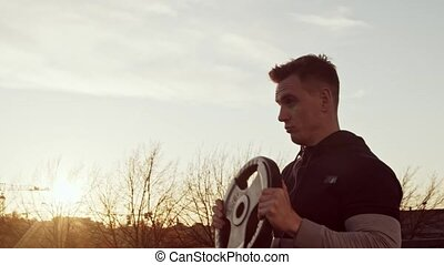Young and fit man having evening workout outdoor. Urban sunset background. Fitness and sport concepts.