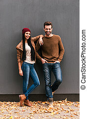 Young and free. Beautiful young couple bonding to each other and smiling while leaning at the grey wall with fallen leaves laying around them