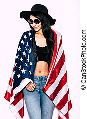 Young and free. Beautiful young mixed race woman carrying American flag on shoulders and looking away with smile while standing against white background