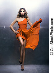 Young and gorgeous woman dancing in a fashion dress