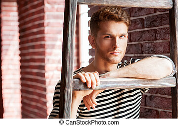 Young and handsome. Handsome young man in striped shirt leaning at the wooden ladder and looking at camera while standing near the brick wall