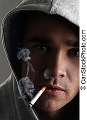 Young and handsome man in hood smoking