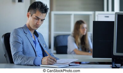 Young and handsome man is making notes sitting in office.