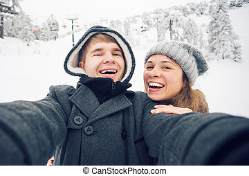 Young and happy couple doing winter selfie outdoor. Christmas, New Year and people concept