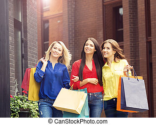 Young and happy women with shopping bags in the city -...