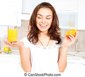 Young and Healthy Woman with Orange Juice in the Kitchen