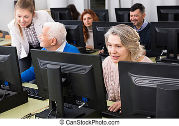 Young and mature men and women coworkers sitting, working on computers