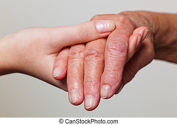young and old hand with a walking cane