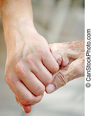 Young and Old - Young woman gives her grandma her hand