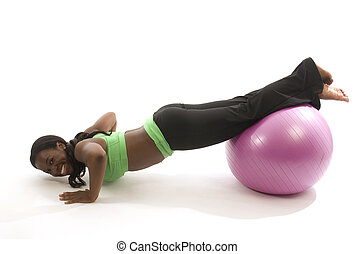 young and pretty hispanic latina black woman wearing exercise tights and working out lifting dumbell weights with fitness core ball