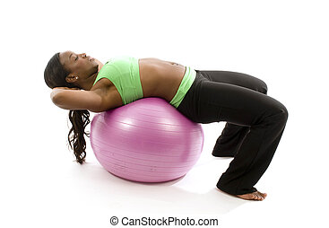 young and pretty hispanic latina black woman trainer wearing exercise tights and working out sit ups with fitness core ball