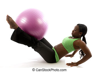 young and pretty hispanic latina black woman wearing exercise tights and working out  leg raises ab exercises with fitness core ball