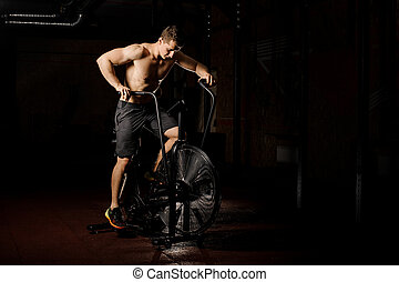 Young and sexy man practicing crossfit using an exercise bike in a gym