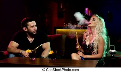 young and sexy people smoking hookah in the lounge caffee,...