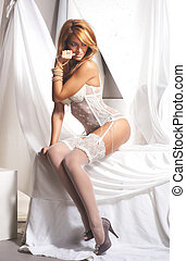 Young and sexy redhead woman in white lingerie