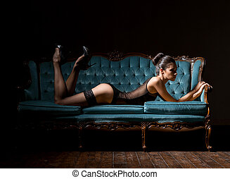 Young and sexy woman in lingerie on a vintage sofa - Sensual...