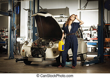 Young and sexy woman repairing a retro car in a garage