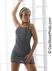 young and sexy woman wearing a mini dress near a back light wall