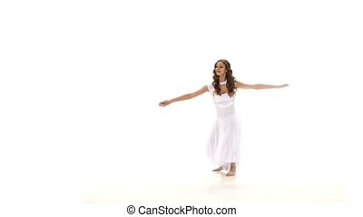 Young and slim woman in light dress dancing contemp jazz...