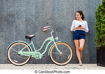 Young and stylish. Beautiful young smiling woman standing near her vintage bicycle on the street