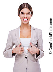 Young and successful. Beautiful young woman looking at camera and showing her thumbs up while standing against white background