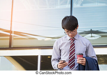 Young and successful businessman is reading a message on his smartphone