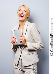 Young and successful businesswoman. Beautiful young businesswoman holding digital tablet and looking up while standing against grey background