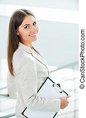Young and successful businesswoman. Rear view of beautiful young smiling businesswoman in formalwear walking by staircase and looking over shoulder