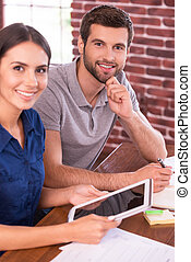 Young and successful. Top view image of cheerful young man and woman sitting at the working place and smiling while woman holding digital tablet
