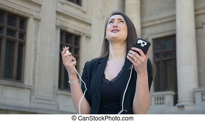 Young angry and anxious woman crying while her phone turns off while due to discharged low battery in the city