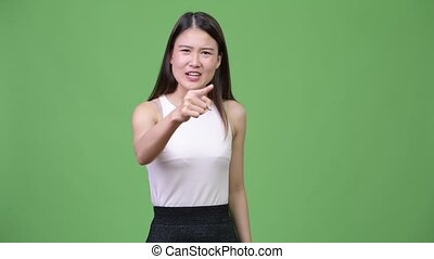 Young angry Asian businesswoman talking to camera