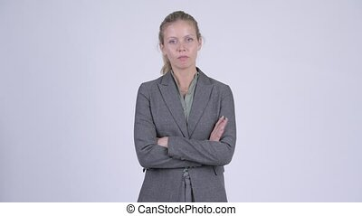 Young angry blonde businesswoman with arms crossed