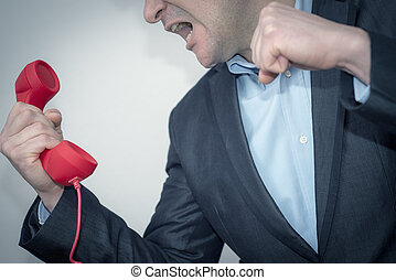 Young angry businessman with phone