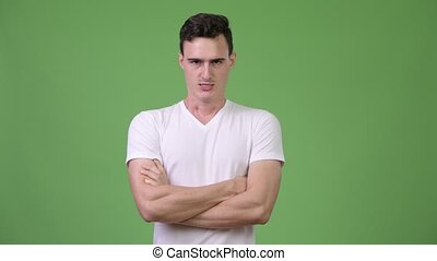 Young angry man with arms crossed - Studio shot of young...