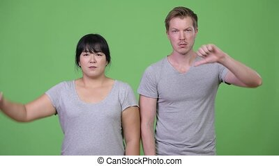 Young angry multi-ethnic couple giving thumbs down together