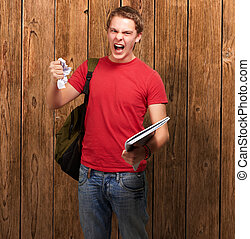young angry student man roughing a sheet against a wooden wall