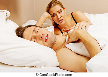 Young angry woman talking to her sleeping husband