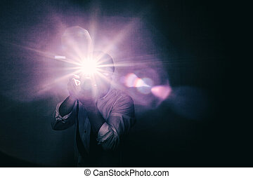 Young annoying fashion photographer in white shirt with sleeves rolled up, trying to take picture with flash in a dark room. Lenses flare, noise and antique stylized.