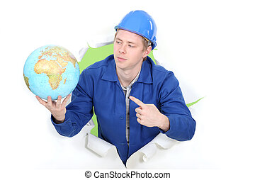 young apprentice in jumpsuit pointing at globe