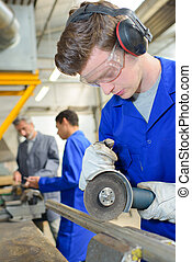 young apprentice using a metal cutter