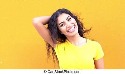 Young Arab Casual Woman on yellow wall in the street smiling...