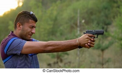 Young arab man is shooting from a gun, close up. Slow motion