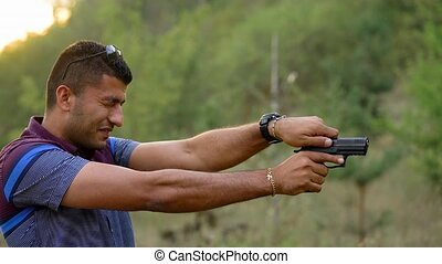 Young arab man is shooting from a gun, close up - Young arab...