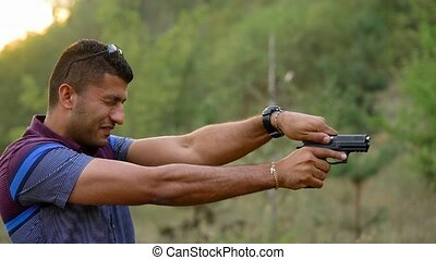 Young arab man is shooting from a gun, close up. Slow motion...