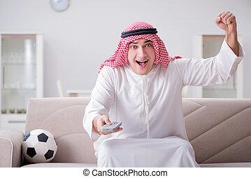 Young arab man watching football sitting on sofa