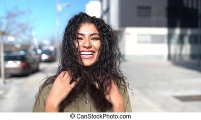 Smiling young Arab woman moving her black curly hair in casual clothes in the street.