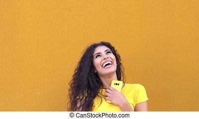 Young Arab Woman on yellow wall in the street smiling and ...