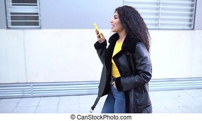 Young Arab woman wearing casual clothes, walking in the street recording voice note with her smartphone. Slow motion
