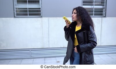 Young Arab woman wearing casual clothes, walking in the street recording voice note with her smartphone.